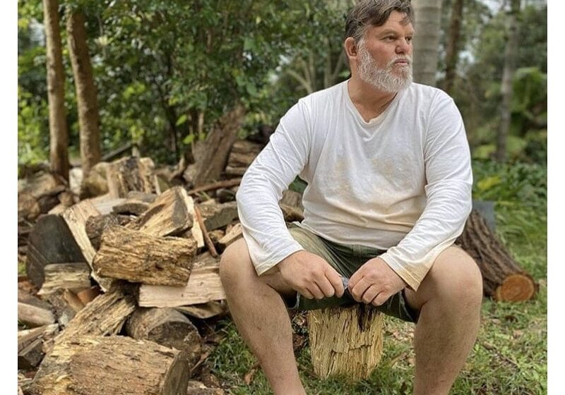 Tim sitting on a wooden log