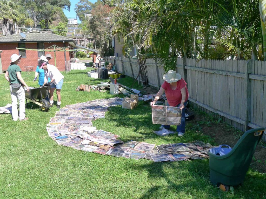 Members laying wet newspaper on the lawn
